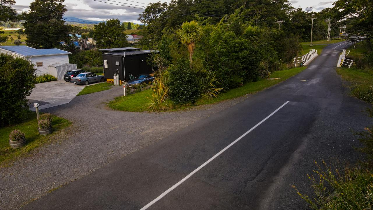 Drone view of Two Rivers Ohakune showing the quiet road, we are located just after the white bridge.  To the right of the picture is a 10 minute riverside walk back to town.
